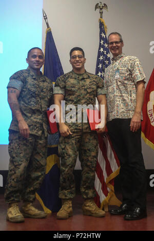 Sgt. Maj. Phillip Billiot, the sergeant major of Headquarters Battalion, Cpl. Paul Franco, a rifleman with 3rd Battalion, 3rd Marine Regiment, and Steve Auerbach, a Solar Ready Vets course instructor, pose for a photo during the SRV graduation ceremony at the theater aboard Marine Corps Base Hawaii on May 11, 2017. The six-week course provided the Marines with basic knowledge of photovoltaic systems and prepared them for the North American Board of Certified Energy Practitioners PV Associates exam. Upon completion of the exam, the Marines will be qualified for solar energy related occupations. - Stock Photo