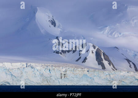 Glacier covered mountains of Greenwich Island, from the sea, bright yet misty weather, South Shetland Islands, Antarctica, Polar Regions - Stock Photo