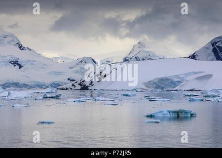 Spectacular mountains, glaciers and blue icebergs of Paradise Bay, water ripples, Graham Land, Antarctic Peninsula, Antarctica, Polar Regions - Stock Photo