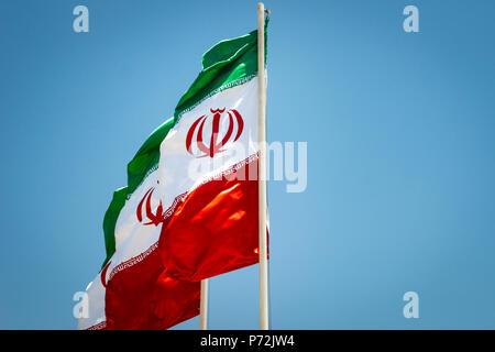 Iranian flags, flags of Islamic Republic of Iran, waving against blue sky - Stock Photo
