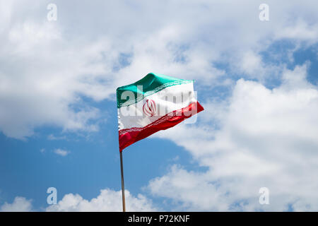 Iranian flags, flags of Islamic Republic of Iran, waving against blue sky - Stock Photo