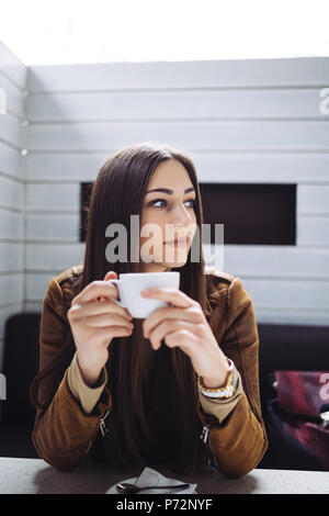 Pretty brunette young woman sitting at cafe bar and drinking coffee. - Stock Photo