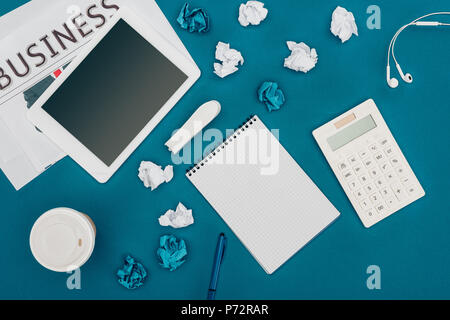 top view of newspaper, digital tablet with blank screen, blank notebook and calculator on blue - Stock Photo