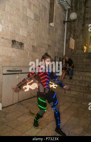 Jerusalem, Israel. 3rd Jul, 2018. A Juggler with a computerized light show creates flames, lions (the emblem of Jerusalem) and other shaped in  the Old city of Jerusalem during the 2018 Festival of lights. This is the 10th anniversary of the festival, festival, israel, jerusalem, Jerusalem. The Festival of Lights in the Old city, jewish, which draws hundreds of thousands of visitors to the old city of Jerusalem, which is lit by many light sculptures and shows Credit: Yagil Henkin/Alamy Live News - Stock Photo