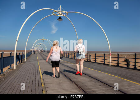 Southport, Merseyside, 4th July, 2018. UK Weather.  Blue skies & bright sun in the north-west as tourists, school children and visitors take a stroll on the seaside pier.  Credit:MediaWorldImages/AlamyLiveNews - Stock Photo