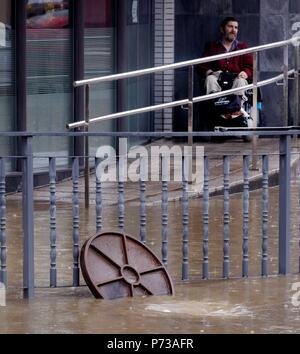 Oviedo, Spain. 04th July, 2018. A man looks at a flooded street in Oviedo, Spain, due to the heavy rains 04 July 2018. Credit: Alberto Morante/EFE/Alamy Live News - Stock Photo