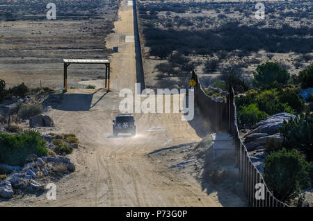 US Border Patrol vehicle beside steel 'landing mat' fence near Jacumba California, looking east, note shade structure on left built for CBP vehicle. - Stock Photo