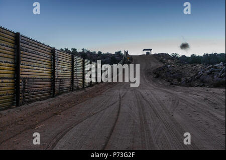 US border fence, old 'landing mat' type, US side looking west at dusk, Border Patrol vehicle under shade structure, Jacumba, California, April 201 - Stock Photo