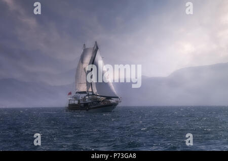 The sight of a sailboat against the background of a morning mist on the shores of the Mediterranean Sea. - Stock Photo