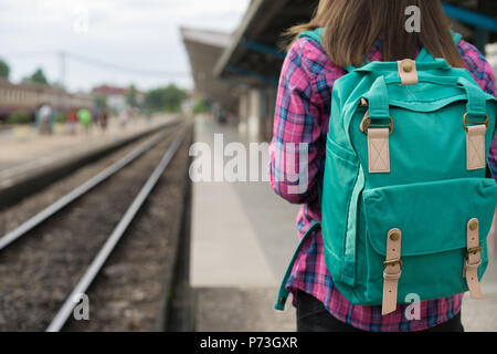 Traveler woman walking and waits train on railway platform, Sun light flare, Selective focus - Stock Photo