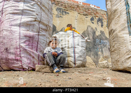 Unidentified children sits near garbage collected sacks in Istanbul, Turkey.09 April 2017 - Stock Photo