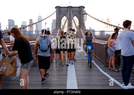 Pedestrians, and cyclists over on the Brooklyn Bridge foot path - Stock Photo