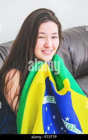Portrait of a smiling woman seated on the home sofa holding the brazilian flag. - Stock Photo