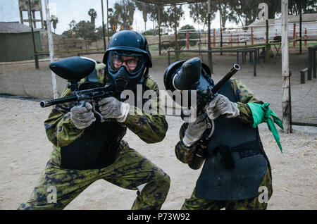 Paintball players in full gear at the shooting range, game weapons - Stock Photo