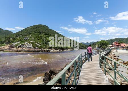 Florianopolis, Santa Catarina, brazil. A tourist man walking on a wooden pier next to the sea on sunny day. - Stock Photo