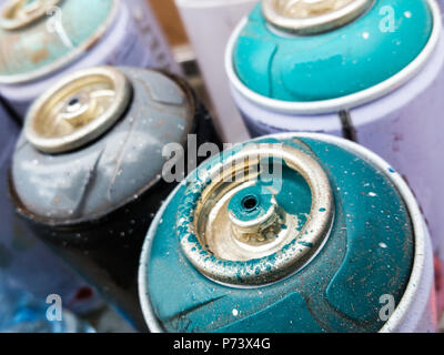 Used cans of spray paint to make urban art on wall. - Stock Photo