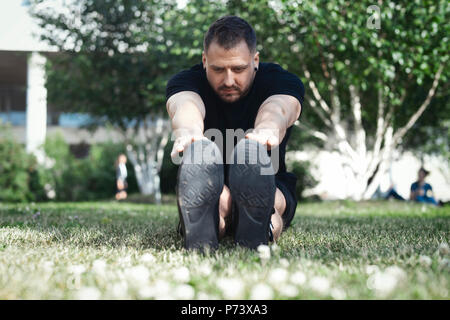 Attractive man in black sportwear doing stretching exercises outdoors in park. - Stock Photo