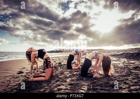 scenic capture with three young beautiful models ladies doing yoga and pilates workout at the beach on the sand. clouds and sunlight during amazing su - Stock Photo