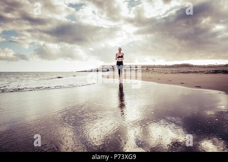 lonely runner lady young caucasian girl at the beach in barefoot style running on the shore. waves and ocean sport activity concept. amazing sunset an - Stock Photo