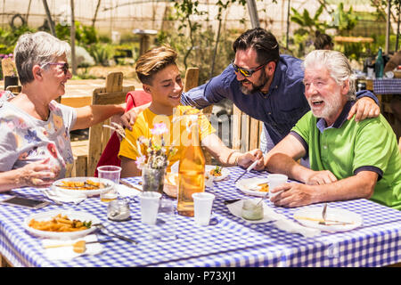 family caucasian people having lunch in natural alternative restaurant all together with joy and fun. smiling and laughing three different generations - Stock Photo