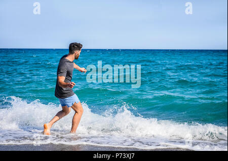 Young Man on Beach Skipping Stones on Sea - Stock Photo