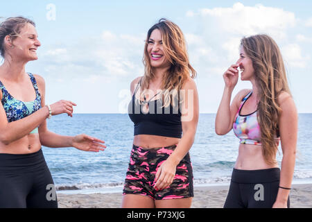 beautiful smiled girls enjoy the sport fitness activity and stay together doing exercises with happiness and a lot of smiles and laugh. women heaving  - Stock Photo