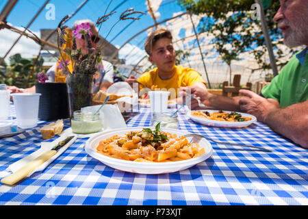 close up of pasta alla norma italian typical food. family caucasian people enjoying an alternative restaurant in the nature outdoor. all bio and veget - Stock Photo