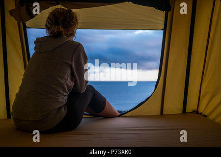 lonely independent strong middle age woman feeling the nature outdoor in a roof tent on the car. travel and lifestyle wanderlust concept for beautiful - Stock Photo