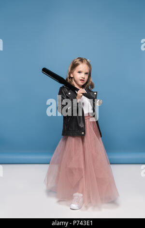 Cute little girl in leather jacket and pink skirt holding baseball bat and looking at camera - Stock Photo