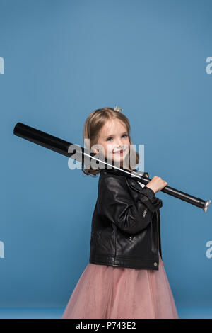 Adorable little girl in leather jacket smiling and holding baseball bat - Stock Photo