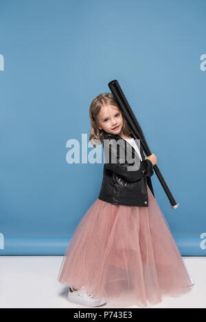 Cute little girl in leather jacket and pink skirt holding baseball bat and smiling at camera - Stock Photo