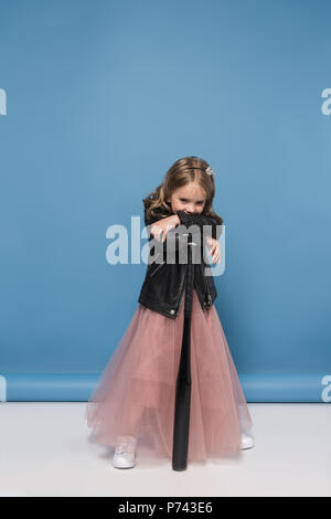 Adorable little girl in leather jacket and pink skirt posing with baseball bat - Stock Photo