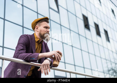 Stylish bearded businessman holding coffee cup by modern building - Stock Photo