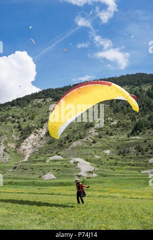 paraglider lands on grassy field between mountains in the frech haute provence - Stock Photo