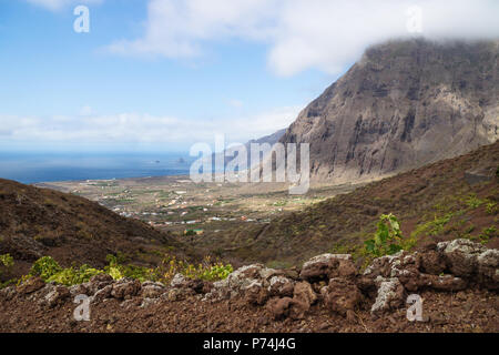 View on the cliffs and red hills of El Golfo valley until the ocean, Frontera, El Hierro, Canary Islands, Spain - Stock Photo