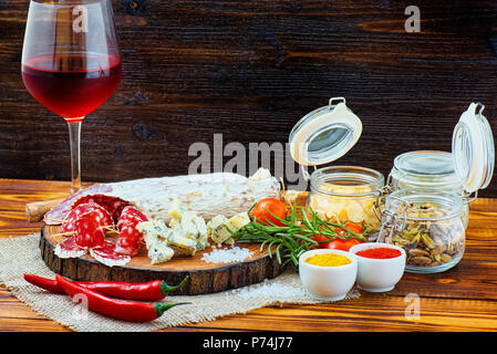 Sliced cured sausage with spices and a glass of red wine on dark wooden rustic background. - Stock Photo