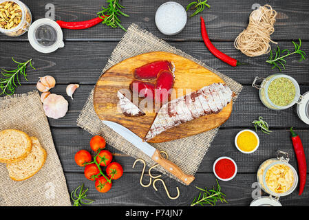 Sliced cured bresaola with spices and a sprig of rosemary on dark wooden rustic background. - Stock Photo