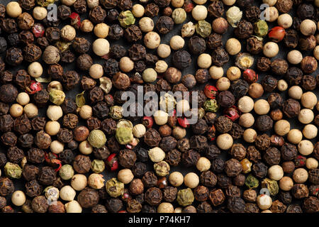 Extreme close up of blend peppercorn mix on a black stone board. Macro food background texture - Stock Photo