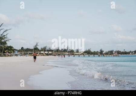 Carlisle Bay beach in Bridgetown, Barbados, unidentified man running along the water. - Stock Photo