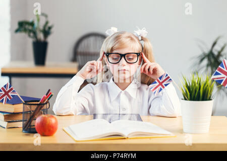 Concentrated girl learning English language using tablet pc in light stylish classroom - Stock Photo