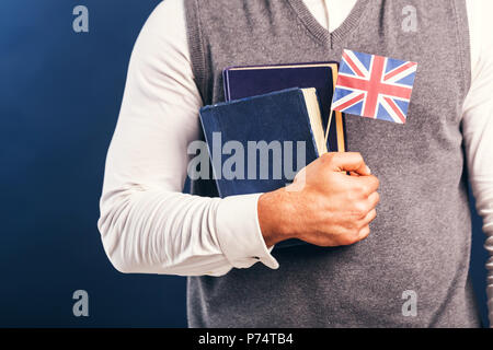 Man wears grey sweater vest holds english books and flag before dark blue studio background, language learning concept - Stock Photo