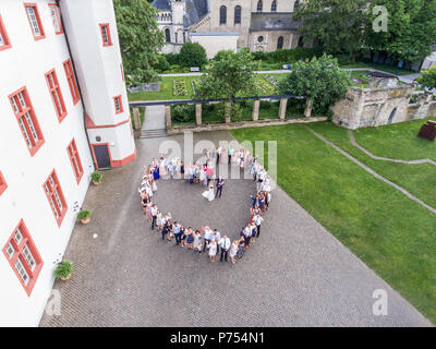 Wedding guests lined up in the shape of heart with bride and groom. marriage people - Stock Photo
