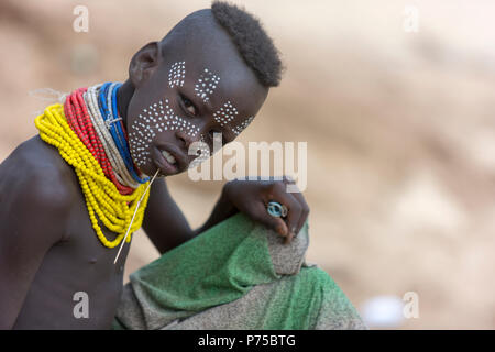 Karo boy poses for a photo.  In his hand is money earned from tourists by posing for such photos. - Stock Photo