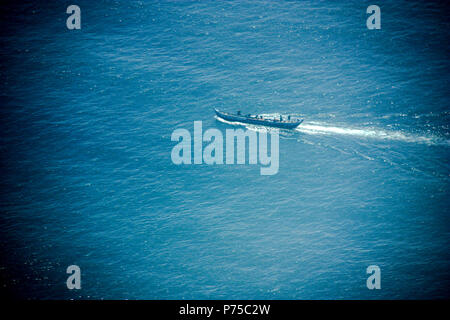 Fisherboat heading for the open waters off the shore of Ghana - Stock Photo