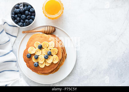 Buttermilk Pancakes with banana, blueberries and honey on concrete background. Top view and copy space for text. Top view of pancakes with berries on  - Stock Photo