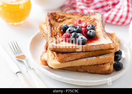 Homemade french toast with fresh berries and honey on white plate, closeup view. Traditional sweet breakfast food - Stock Photo