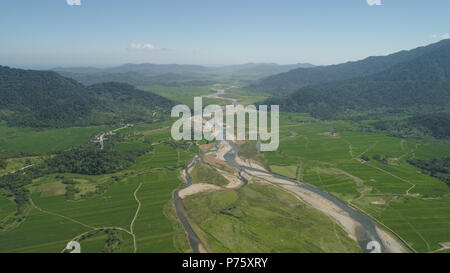 Mountain valley with river, farmland, rice fields. Aerial view of Mountains with green tropical rainforest, trees, jungle with blue sky. Philippines, Luzon. - Stock Photo
