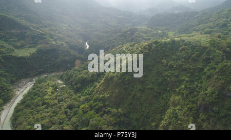 Aerial view of mountain valley with river, rice terraces, farmland in the Philippines, Luzon. Aerial view of mountains covered forest, tree. Cordillera region. - Stock Photo
