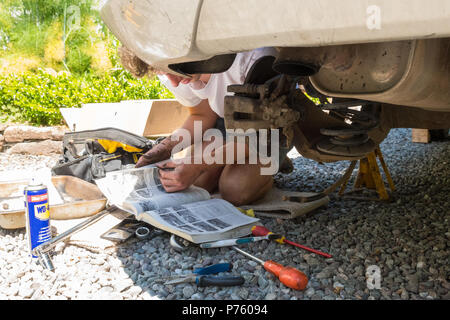 DIY car maintenance and repairs - young man reading Haynes manual as he changes the brake pads, brake disc and brake caliper for the first time - Stock Photo