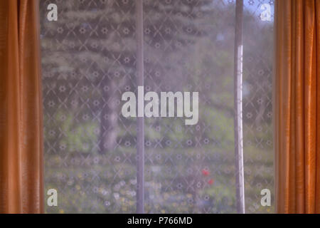 View of a summer garden with large trees and flowers through a patterned curtain tulle. Blurry - Stock Photo